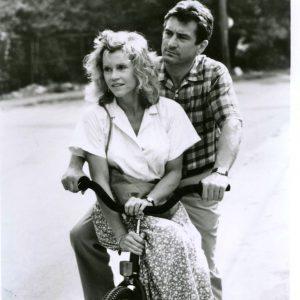 Robert De Niro and Jane Fonda ride a bike.