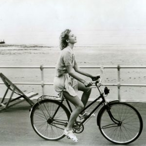 Emily Lloyd rides a bike.