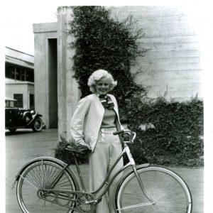 Jean Harlow walks a bike.