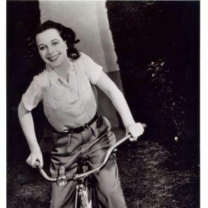 Hedy Lamarr rides a bike.