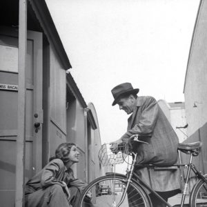 Humphrey Bogart stands by a bike. Lauren Bacall smiles.
