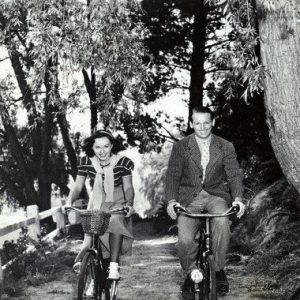 Paulette Goddard and Douglas Fairbanks Jr. ride bikes.