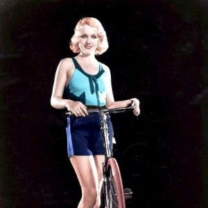 Anita Page stands by a bike.