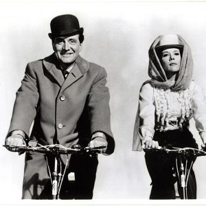 Patrick Macnee and Diana Rigg ride bikes.
