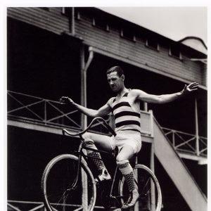 Charley Chase rides a bike.