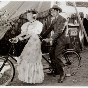 Fay Wray and Gary Cooper ride a bike.