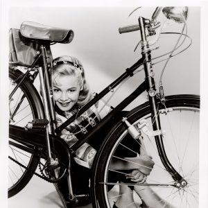 Sandra Dee hides behind a bike.