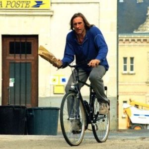 Gerard Depardieu rides a bike. And holds a baguette. Rides a Bike