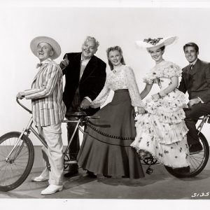 Jimmy Durante, Lauritz Melchior,June Allyson, Kathryn Grayson and Peter Lawford ride a bike.