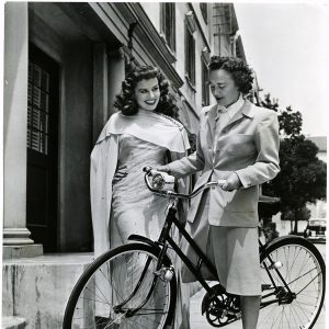 Lenore Sabine, Paramount hair stylist, rides a bike. Paulette Goddard stands by. Rides a Bike