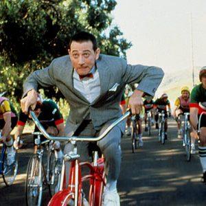 Pee-wee Herman rides a bike.