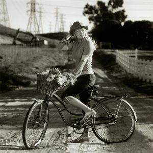 Julia Stiles rides a bike.