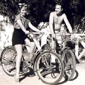 Joan Blondell and Dick Powell ride bikes.