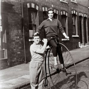 Shirley Anne Field rides a bike. Norman Rossington lends a hand.