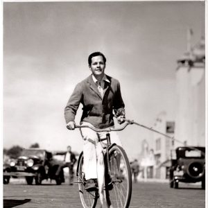 "Donald Woods rides a bike. With a white sea bass. Caption: ""Donald Woods bicycles home from Santa Monica pier with the fish he caught on a recent expedition. The Warner Bros. actor, currently in ""The White Angel,"" is one of the most enthusiastic anglers in the film colony."""
