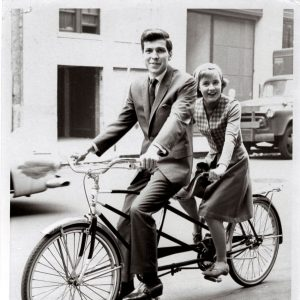 Patty Duke and Frank Sinatra Jr. ride a bike.