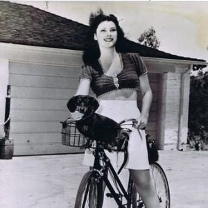 Vicky Lane and daschund ride a bike.