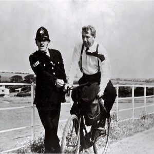 Michael Redgrave rides a bike. Meredith Edwards holds on.