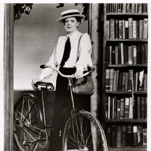Ethel Barrymore walks a bike.