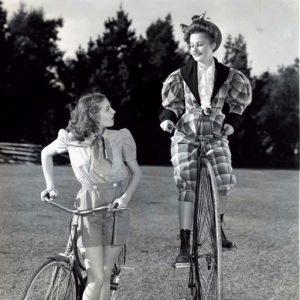 Jo Ann Sayers walks a bike, Lynne Carver rides a bike, loftily.