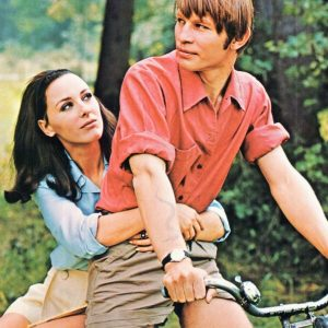 Michael York and Heidelinde Weis ride a bike.