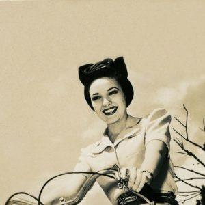 Linda Darnell rides a bike.