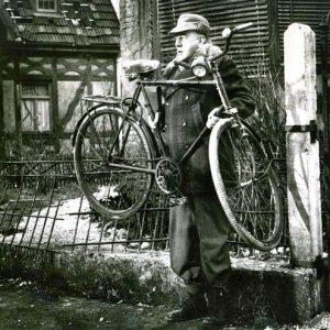 Alec Guinness hefts a bike.