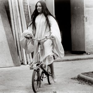 Olivia Hussey rides a bike.