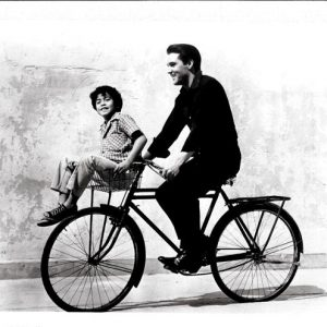 Elvis Presley and Larry Domasin ride a bike.