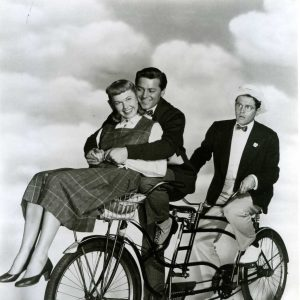 Doris Day, Gordon MacRae and Jack Smith ride a bike.