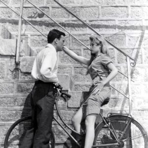 Brigitte Bardot rides a bike. Jean-Louis Trintignant invites her for Thanksgiving.