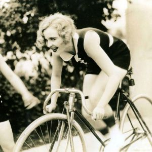 Phyllis Haver rides a bike. Stationarily.