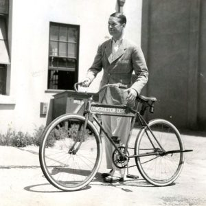 Maurice Chevalier walks a bike. And smokes a cigarette.