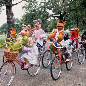 The Muppets ride bikes. Side by side.
