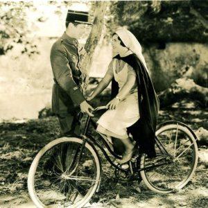June Walker rides a bike. Robert Montgomery gets a grip.