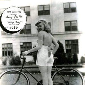 Betty Grable walks a bike, wears a tog.