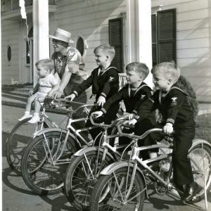 Bing and Lynn Crosby, Gary, Phillip and Dennis Crosby ride bikes.