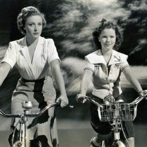 Laraine Day and Shirley Temple ride bikes.