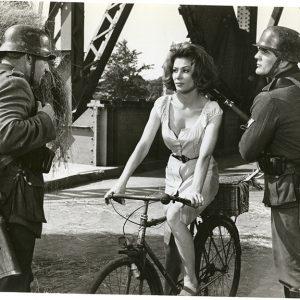 Irina Demick rides a bike. Uh-oh, Nazis.