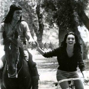 Chuck Connors rides a horse. Kamala Devi rides a bike. Geronimo!