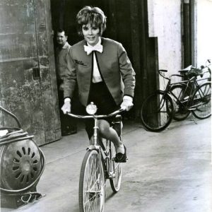 Jill St. John rides a bike.