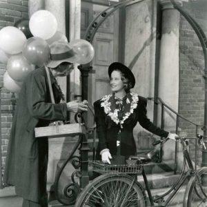 Merle Oberon walks a bike. Balloon man hawks his wares.