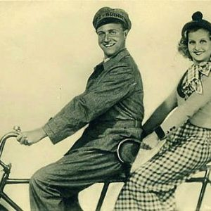 Willy Fritsch and Lilian Harvey ride a bike.
