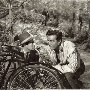 Bruce Lester and Ray Milland hide behind a bike.