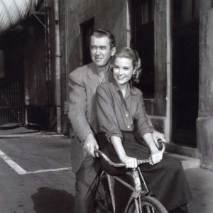 James Stewart and Grace Kelly ride a bike.