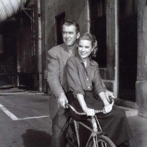 James Stewart and Grace Kelly ride a bike.