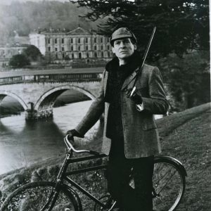 Jeremy Brett walks a bike.