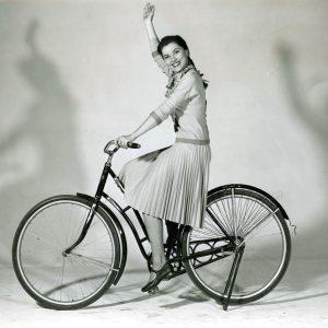 Debra Paget rides a bike.