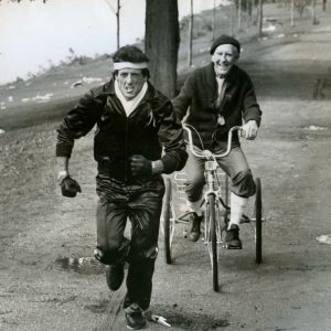 Burgess Meredith rides a trike. Sylvester Stallone trains.