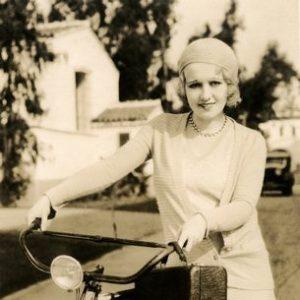 Anita Page walks a bike.
